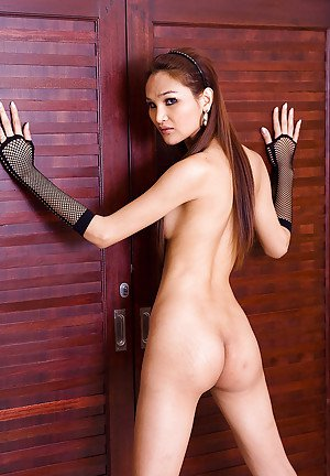 Skinny Thai ladyboy showing off her curved cock in high heels