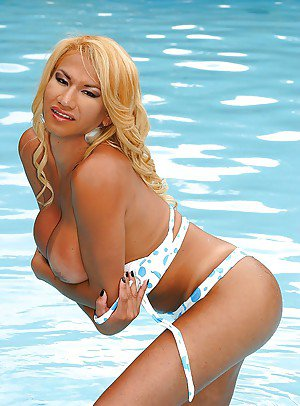 Busty blond Latina tranny Lorena Agua posing in swimsuit in pool