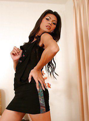 Big ass Asian ladyboy Benz posing on her bed in high heels and a skirt