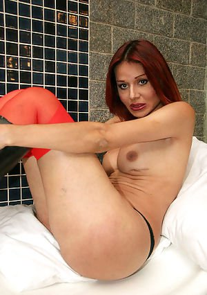 Busty redhead Latina shemale Melisa eating cum in red stockings