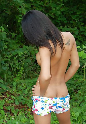 Busty young Asian ladyboy getting naked and spreading outdoors