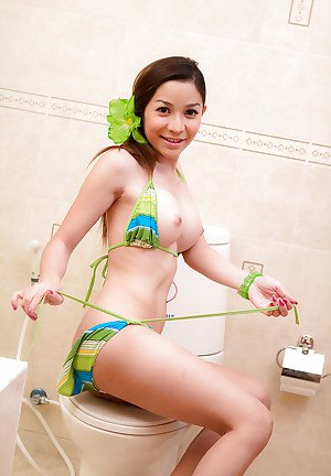 Brunette teen Asian ladyboy Pim toying her hot pussy in the bathroom