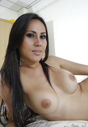 Beautiful and slim Thai ladyboy Bow shows her big tits in the bedroom