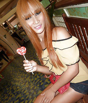 Slender Asian shemale with red hair taking nude selfies of tattooed body