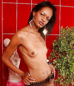 Skinny ebony transsexual Aline de Oliveira showing off nice ass and tattoos