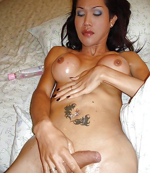 Busty Asian shemale Lek jerking off shaved shecock with help from oil